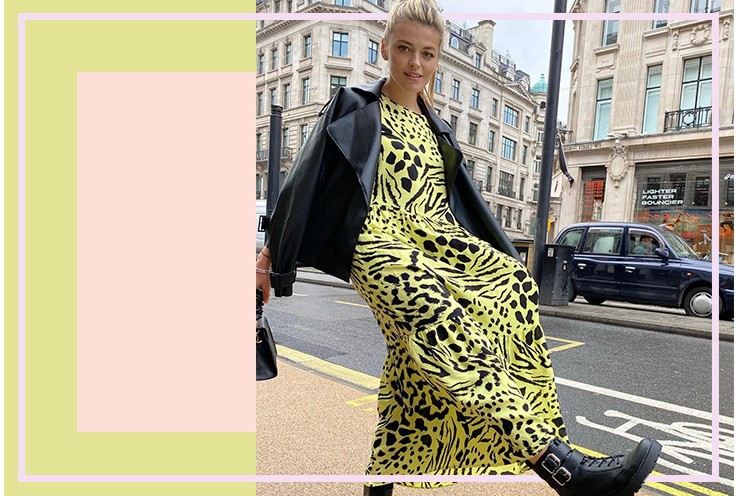 Woman kicks into the air with one foot wearing a yellow and black animal print maxi dress, black faux leather jacket and black biker boots on a main road with buildings and black cab in the background.