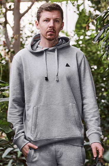 Professor Green posing in a grey hoodie and joggers set.