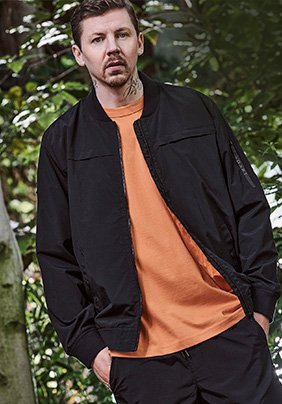 Professor Green poses with hands in pockets wearing black jacket, orange top and black trousers.