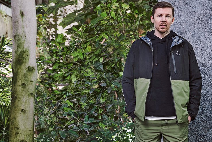 Professor Green stands in front of a wall wearing black hoodie, black and khaki coat and khaki trousers.
