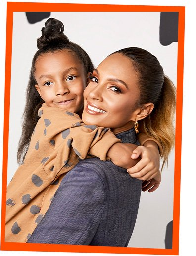 Alesha Dixon wearing a denim shirt holding a young girl wearing a tan abstract spot print jumper.
