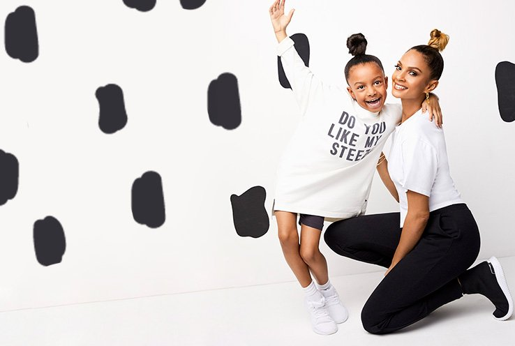 Alesha Dixon crouches on floor smiling wearing white t-shirt, black jeans and black trousers next to girl waving hand in the air wearing white slogan top, shorts and white trainers.