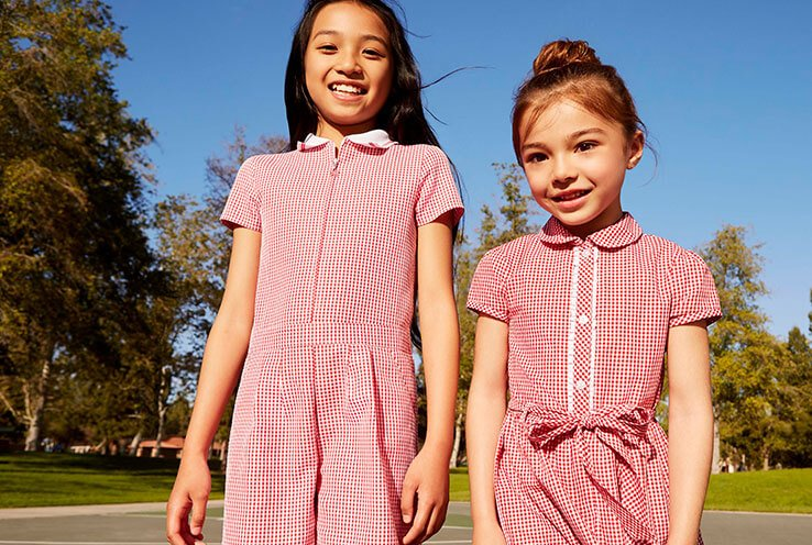 Two school girls outside wearing different styles of a red gingham dress