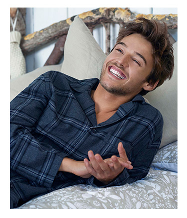 A male model wears dark blue check pyjamas
