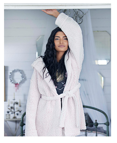 Female model wearing pyjamas and white dressing gown