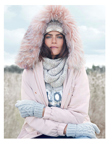 A model wears a pink parka with gloves, scarf and knitted hat