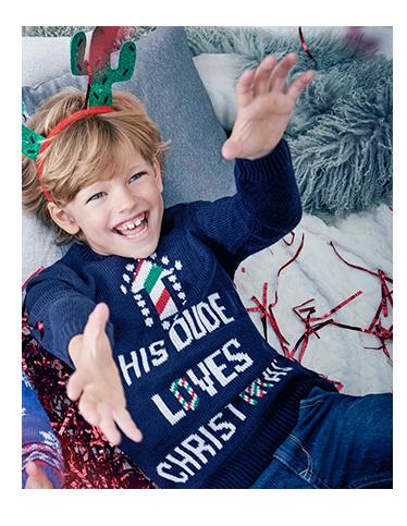 A boy wears a blue Christmas jumper