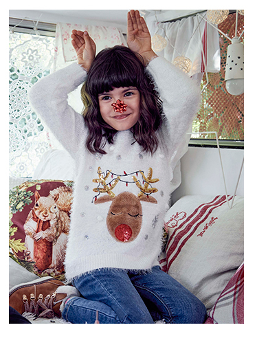 A girl wears a white reindeer Christmas jumper