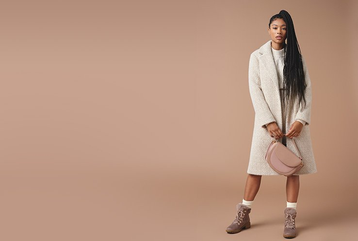 Woman with long black hair poses wearing natural textured longline formal coat, cream cable knit jumper, pink handbag, pink boots and white socks.
