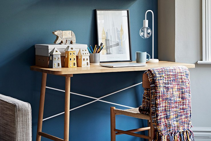 A wooden desk topped with a selection of ceramic house ornaments, a polar bear calendar, a lamp, a picture frame and a mug, with a matching wooden chair with a multicoloured throw draped over the back