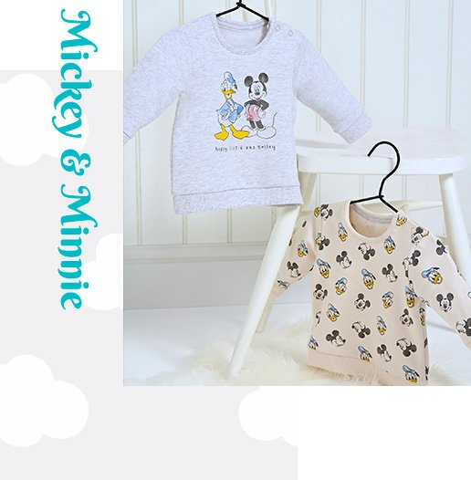 Two Disney jumpers with Donald Duck and Mickey Mouse designs hanging from a white chair on black hangers.