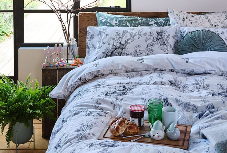 White bunny printed duvet set with green scatter cushion topped with a wooden tray with hot crossed buns, strawberry jam, bunny patterned egg cups, green tumbler and white mug.
