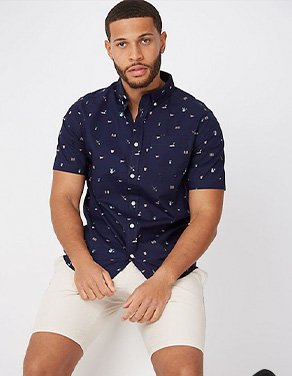 Man sitting wearing a navy gardening print shirt with cream shorts