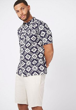 Man wearing a black and white printed linen blend shirt with cream shorts