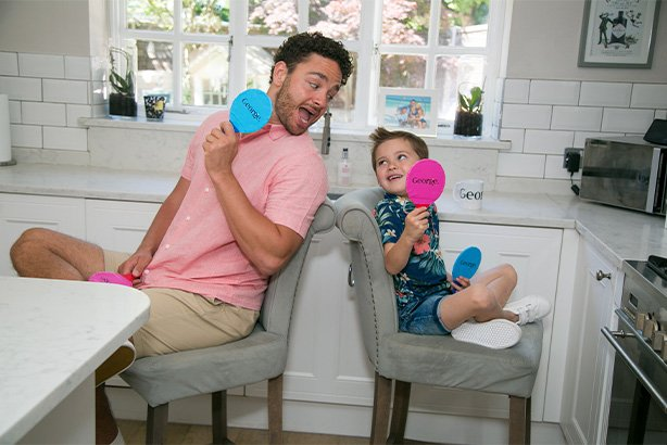 Adam and Teddy sitting back to back holding blue and pink paddles