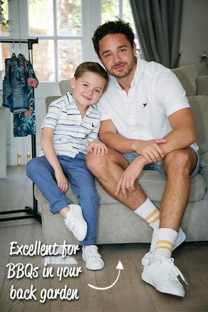 Adam wearing a white patterned shirt, grey shorts and white sneakers with Teddy in a white and blue striped polo, blue chinos and white sneakers sitting on a sofa