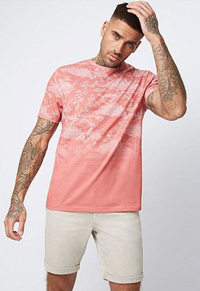 Man wearing a coral ombre t-shirt and cream chino shorts