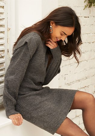 A woman sitting down wearing grey knit jumper dress.