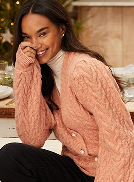A smiling woman wearing a cream turtleneck, pink knitted cardigan and black trousers.
