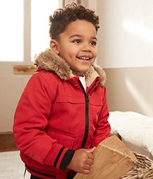 A smiling boy wearing a red faux fur lined coat.