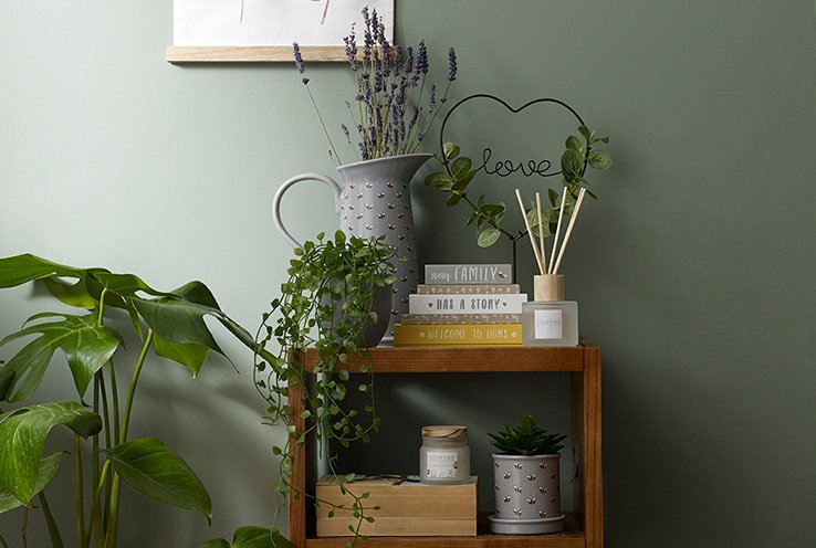 Wooden table in green room with books, candles, a jug vase, artificial plants and a love wire sign with artificial leaves.