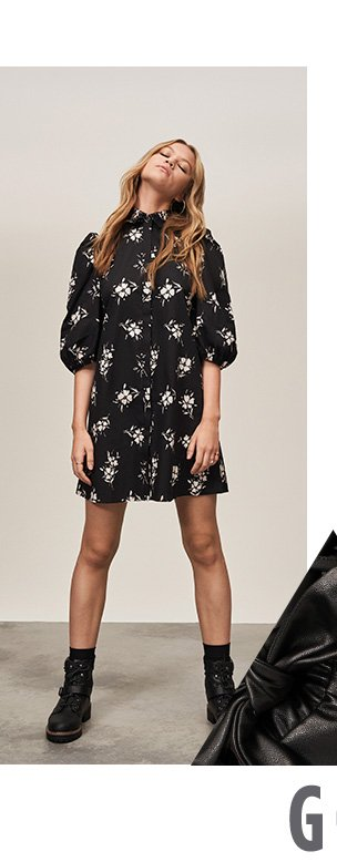 Woman with dark blonde hair poses with head back wearing black floral puff sleeve mini dress and black biker boots.