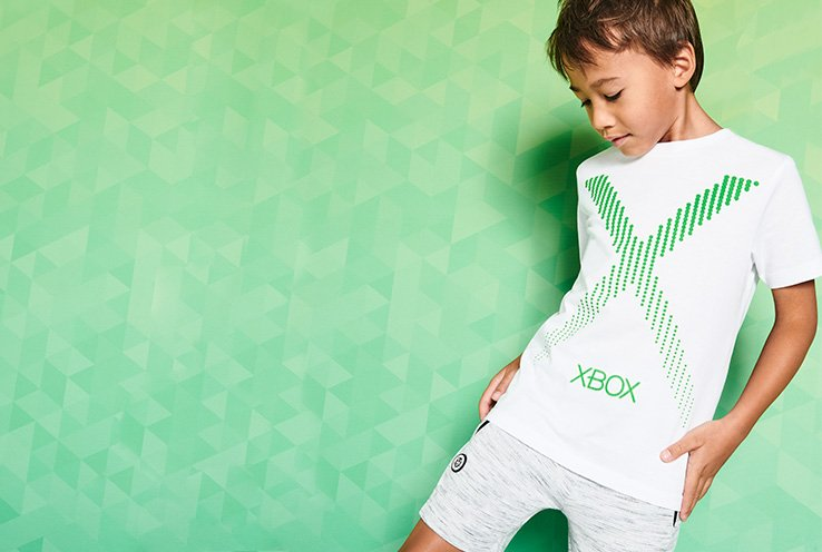 A boy wearing grey shorts and a white Xbox logo print t-shirt