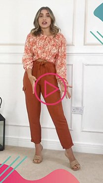 Emily Moloney wearing an orange palm print blouse, burnt orange paper bag waist trousers and woven sandals