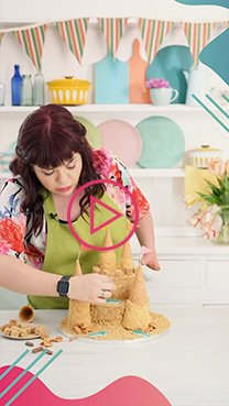Briony wearing a floral blouse and green apron putting the final touches onto a sandcastle cake