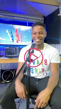 Donel Mangena wearing an NHS slogan t-shirt, sitting in front of a microphone