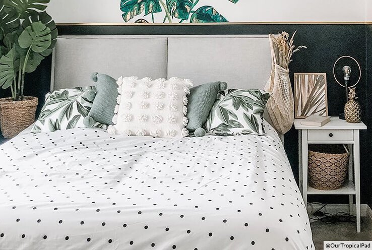 A double bed with a spotted duvet cover set and matching plant-print cushions
