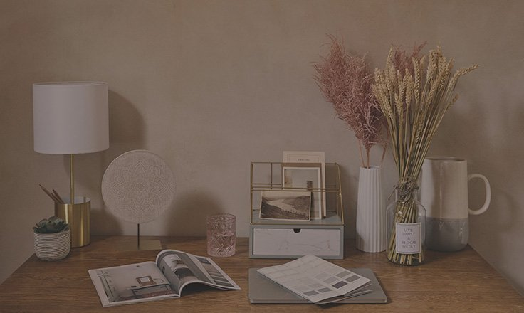 Wooden table with gold-tone storage lamp, artificial plant, an open magazine, grey storage box and a cream vase, glass vase and cream and grey vase with handle.
