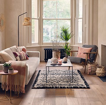 Living room with large open windows featuring cream sofa, grey chair with pink and cream scatter cushions, coffee table, cream textured rug and rattan floor lamp.