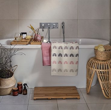 White freestanding bath with wooden-effect bath trays and rainbow printed towels draped over the edge surrounded by a wicker table topped with a storage basket, wooden duck board, artificial plant and amber candle and diffuser set.