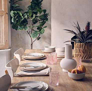 Wood-effect dining table with cream place settings, rose-tinted tumblers, white bowl containing peaches, white vase and artificial plant in a wicker basket.