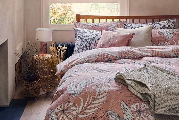 Double bed with dusky pink floral bedding, plain and floral scatter cushions and a grey textured throw.