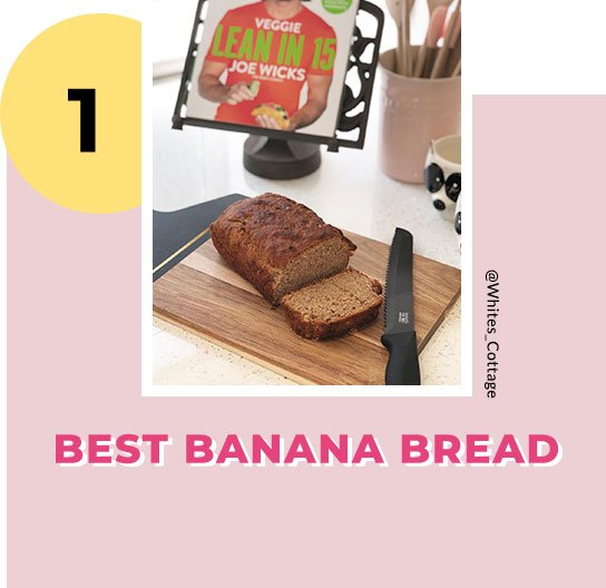 A fresh loaf of banana bread on a chopping board next to a bread knife, with a Joe Wicks cookbook in the background.