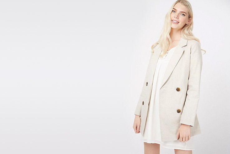 Woman wearing a stone linen blend double breasted blazer over a white shift dress