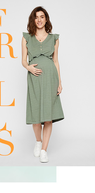 Pregnant woman wearing a khaki frill cap sleeve midi dress with white trainers