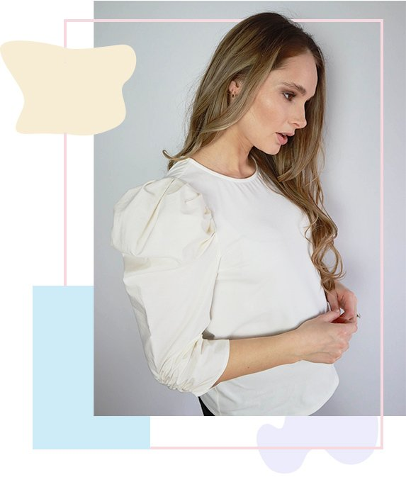 Side profile of woman wearing white long sleeved blouse with ruched shoulders.