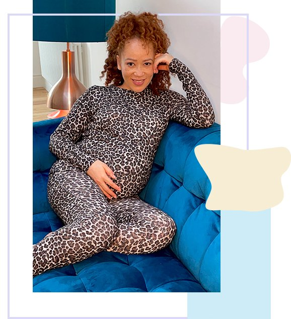 Woman sits with feet up on blue sofa smiling wearing grey leopard print matching long-sleeved top and leggings.