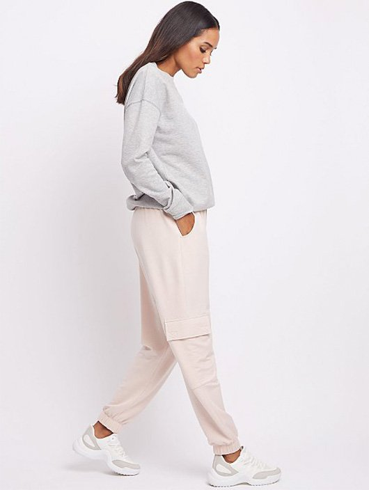 Woman wearing a grey jumper and pink joggers with white trainers