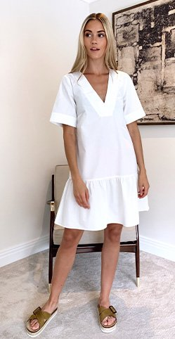 Model Meg wearing a white thrill dress with sandals