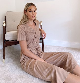 Model Meg wearing a brown jumpsuit with tie waist and buttons