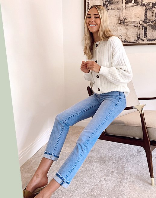 Model Meg wearing a white button up cardigan with light blue jeans