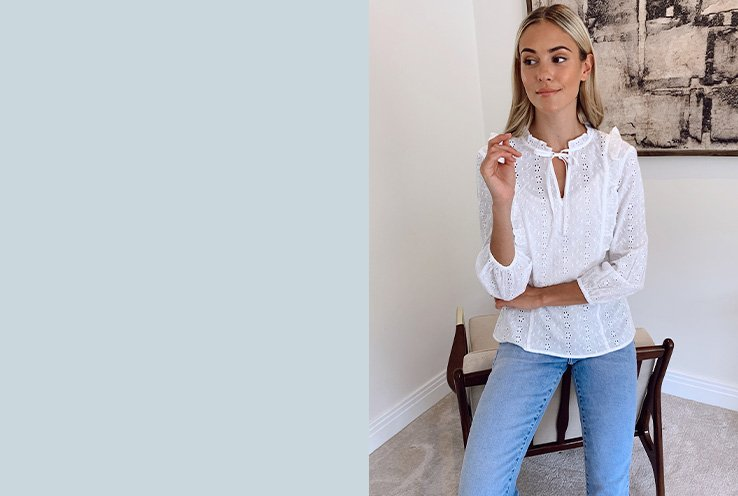 Model Meg wearing a white blouse with light blue jeans