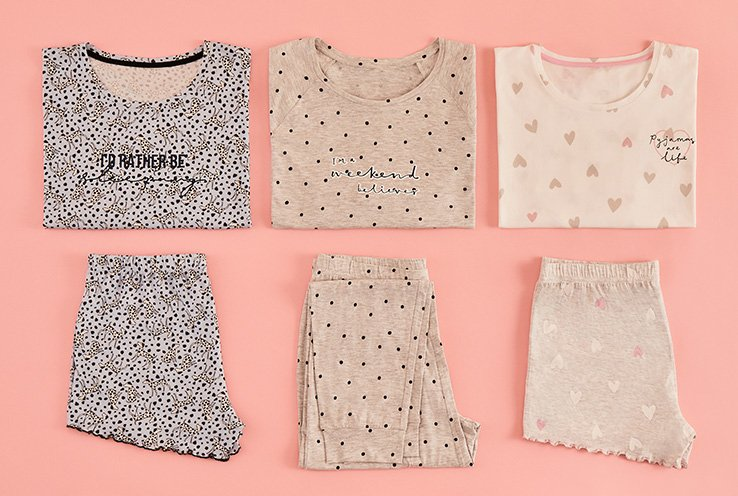 Folded brown animal print pyjama shorts set, folded natural polka dot print pyjama shorts set, and folded pink heart print pyjama shorts set on a light pink background.