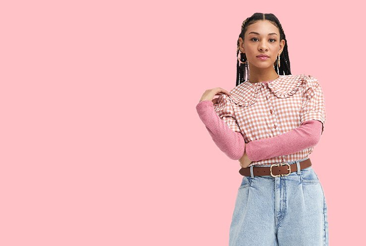 Woman poses wearing a long sleeved pink top under a pink and white gingham check print collared blouse, light blue acid wash jeans with tan gold-tone buckle belt and gold-tone hoop earrings.