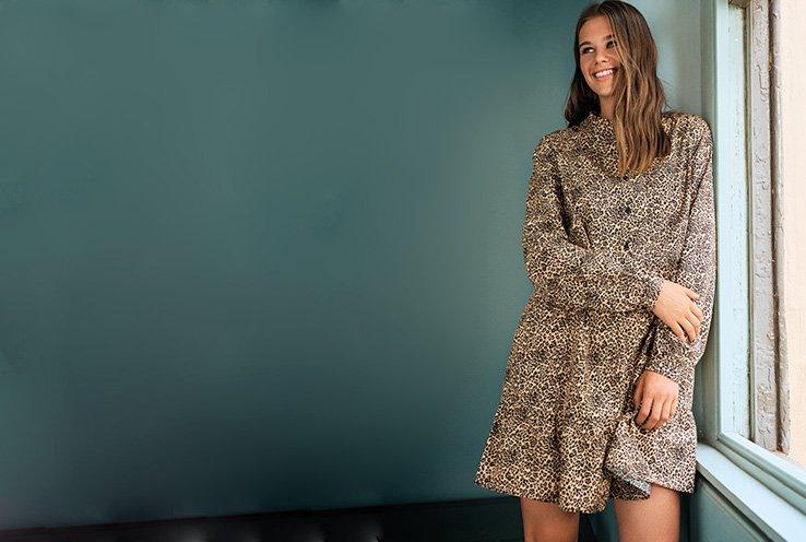 Woman leaning against a window sill wearing a long sleeve leopard print dress