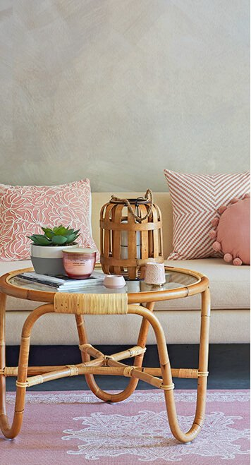 A round bamboo coffee table topped with a selection of candles, succulent planters and magazines, in front of a cream sofa with pink accent cushions